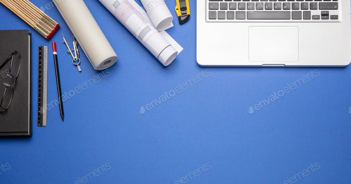 Project blueprints, stationery and computer laptop on blue color, top view