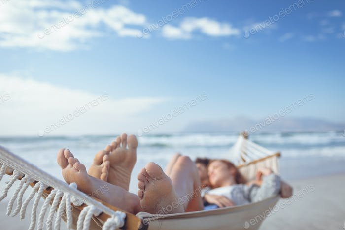 Front view of relaxed Caucasian couple sleeping on hammock at beach on sunny day
