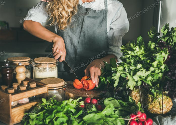 Woman cutting fresh tomatoes on concrete kitchen counter