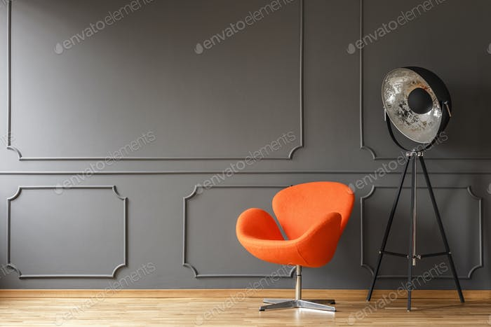 Orange armchair next to lamp in minimal living room interior wit