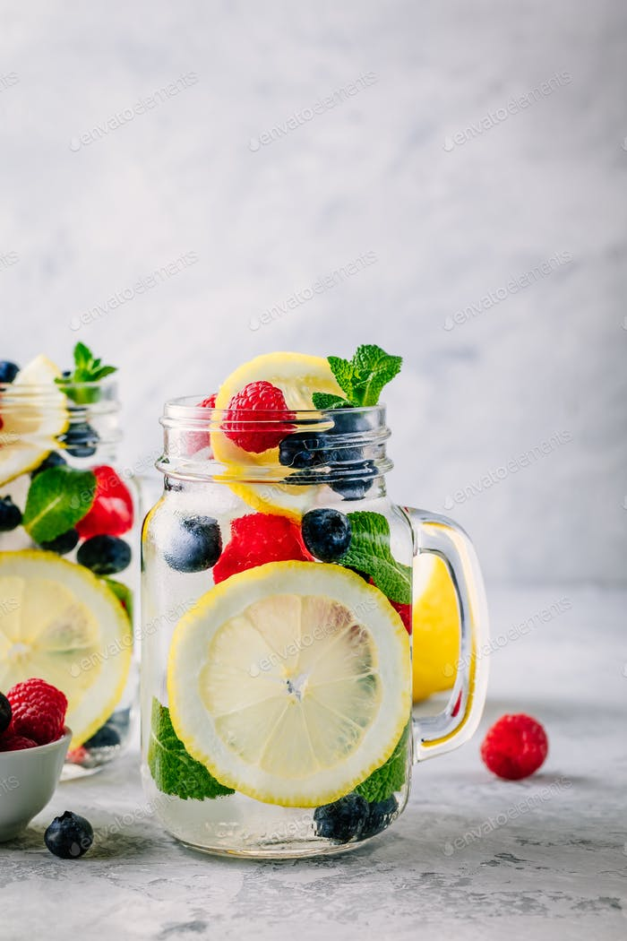 Infused detox water with lemon slice, raspberry, blueberry and mint.