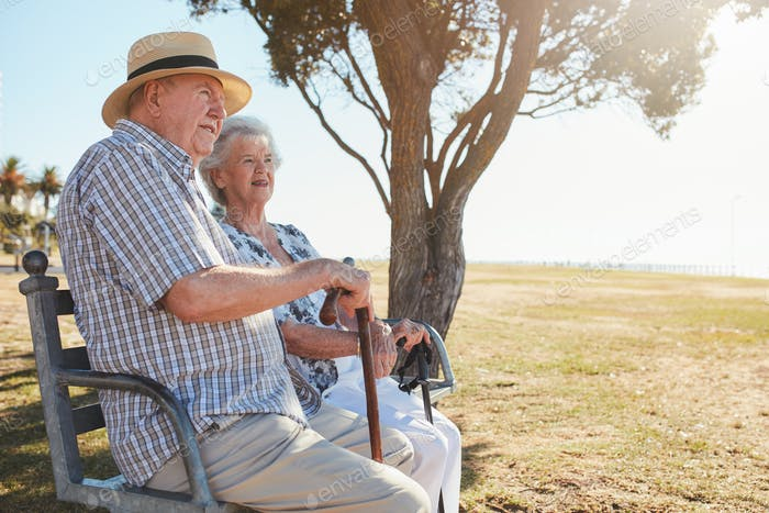 Senior man and woman sitting on a park bench outdoors