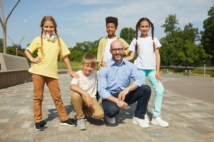 Kinder posieren mit männlichen Lehrer im Freien