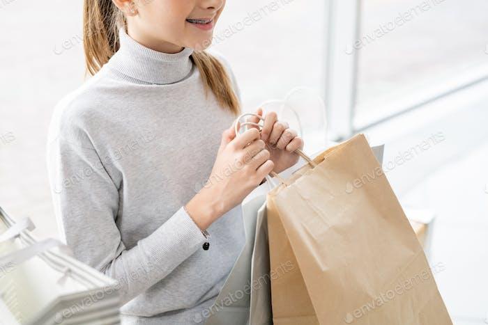 Mitte Abschnitt der niedlichen Mädchen in Freizeitkleidung halten Paperbag mit Kauf