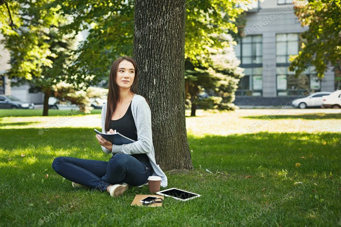 Young woman sitting with notebook on grass