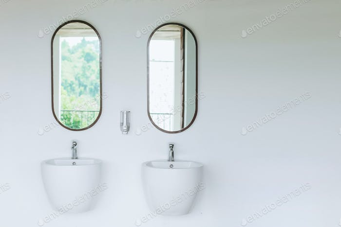 Two white sink on white wall