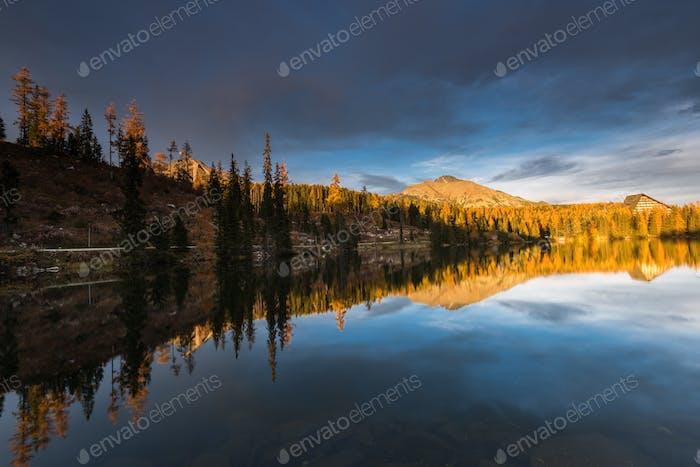 Stnning sunset last golden light over alpine lake nad peaks