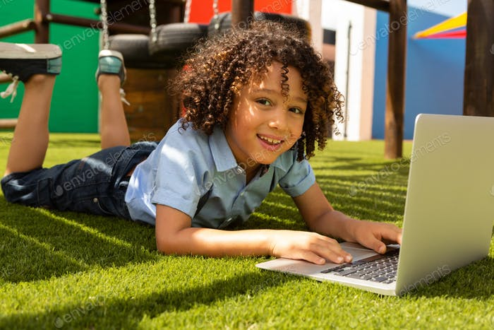 Happy schoolgirl using laptop and looking at the camera on the school playground