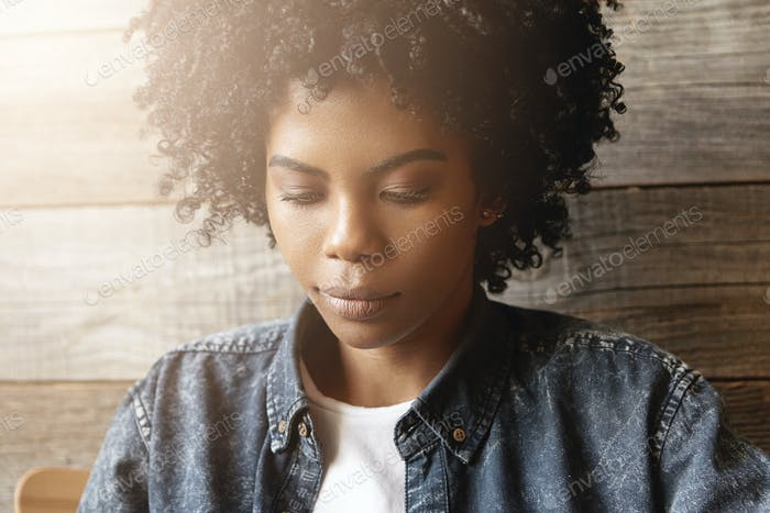 People, lifestyle, beauty and fashion. Beautiful fashionable dark-skinned girl with curly hair and p