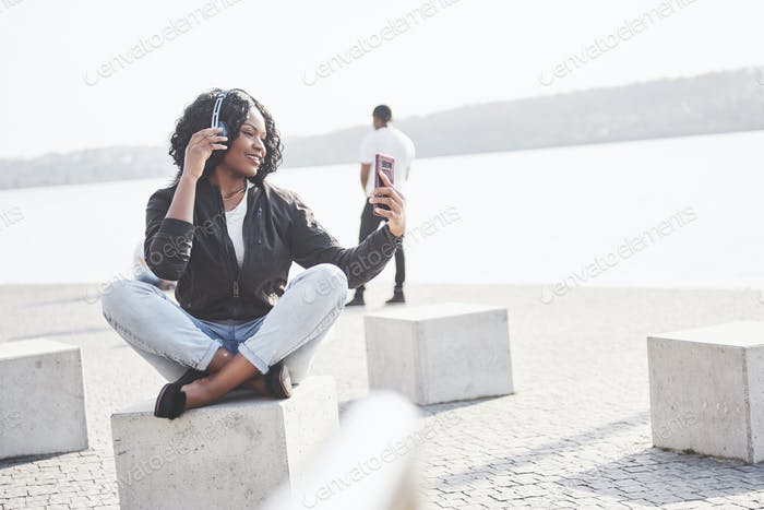 Portrait of a beautiful young pretty African American girl sitting on the beach or lake