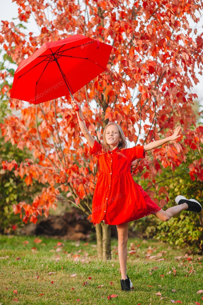 Happy child girl laughs under red umbrella