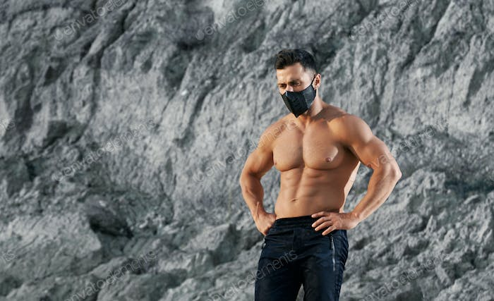 Powerful man in protective mask posing outdoors