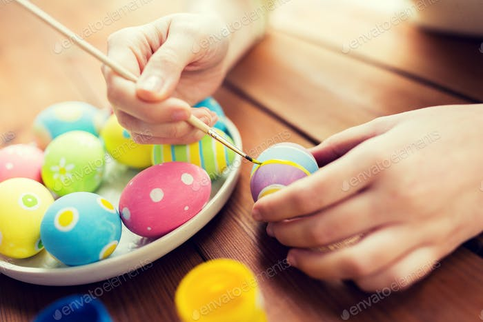 close up of woman hands coloring easter eggs