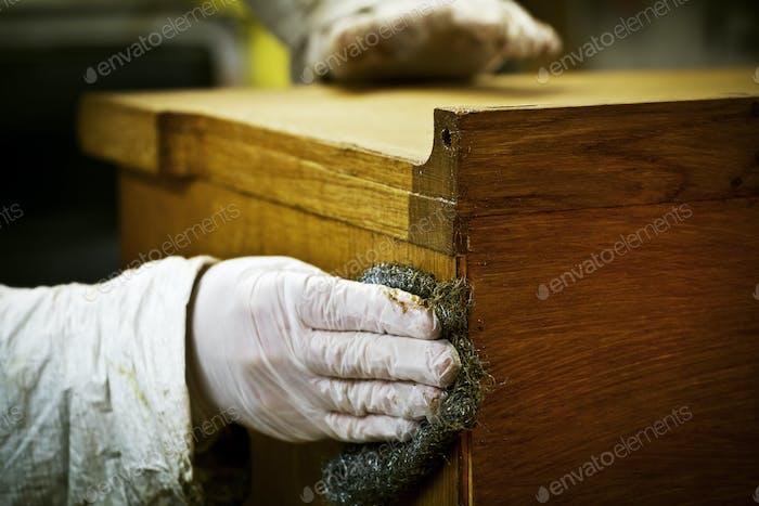 Una persona con guantes usando lana de alambre para lijar o encerar un mueble.