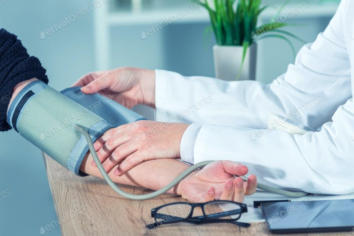 Doctor cardiologist measuring blood pressure of female patient