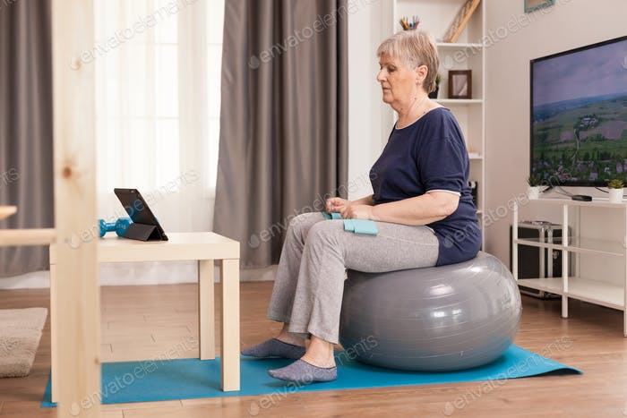 Elderly woman learning sport online