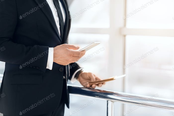 Unrecognizable businessman using smartphone, holding passport and tickets