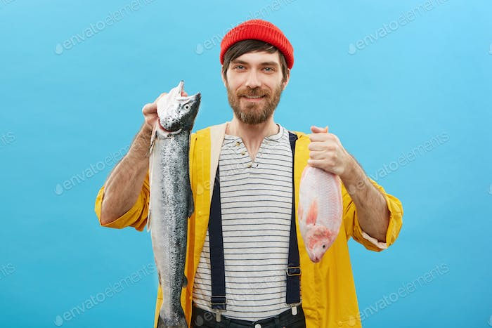 Glad male angler with beard and mustache holding his trophy feeling surge of pride. Succesful unshav