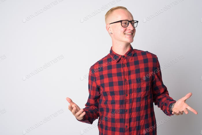 Portrait of happy young blonde hipster man with arms raised