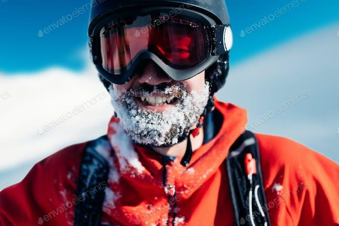 glücklich Snowboarder steht im roten Anzug