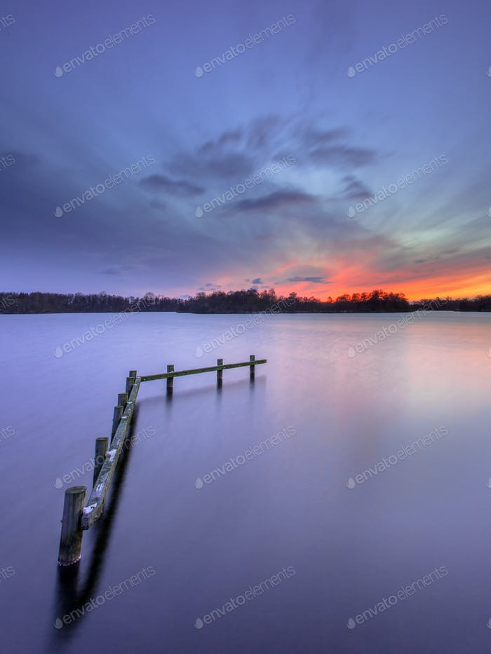 Purple Sunset over Wooden Construction in Tranquil Lake