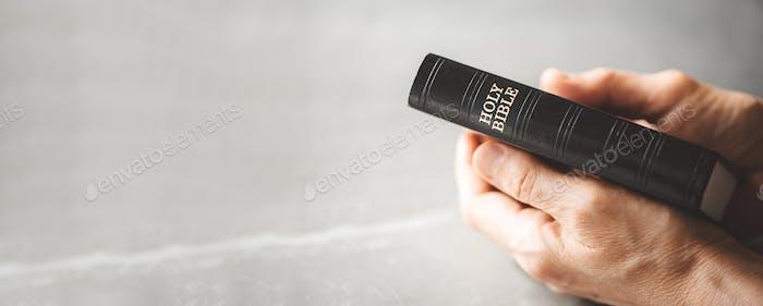 Hände halten die Bibel über grauen Hintergrund. Das Evangelium mit den Jugendlichen teilen. Raum kopieren.  Christian