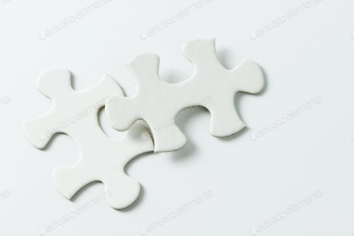 Two pieces of white jigsaw puzzle