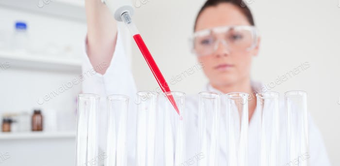 Beautiful red-haired scientist filling up a test tube