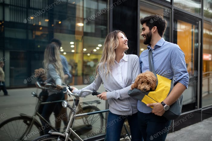 Beautiful couple walking dogs and bicycles outdoors in city