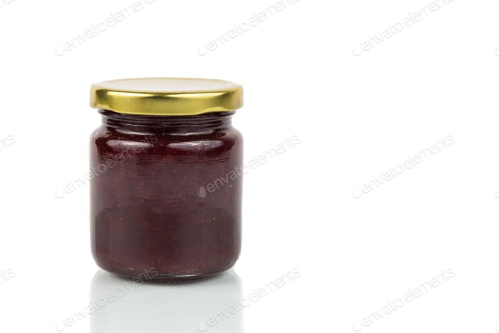 Organic strawberry jam in transparent glass jar