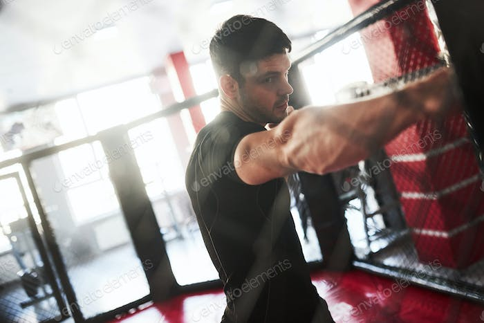 Strong man is boxing in the gym behind the fence. Haves daily exercise