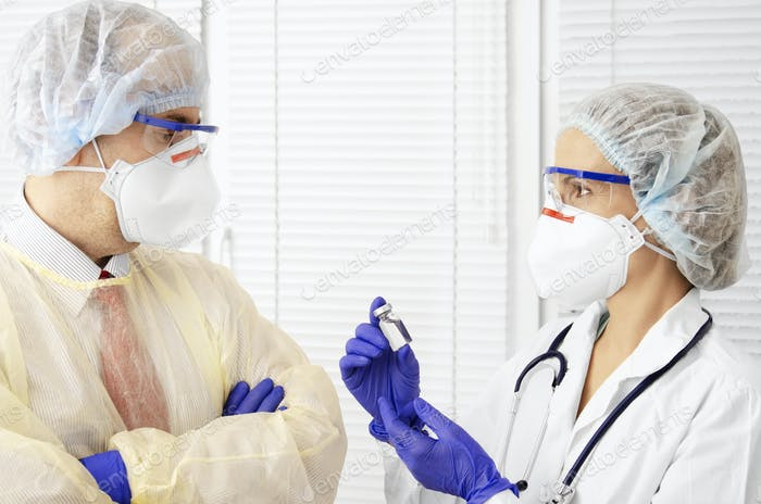 Male and female health care workers in masks caps and gloves having discuss indoors