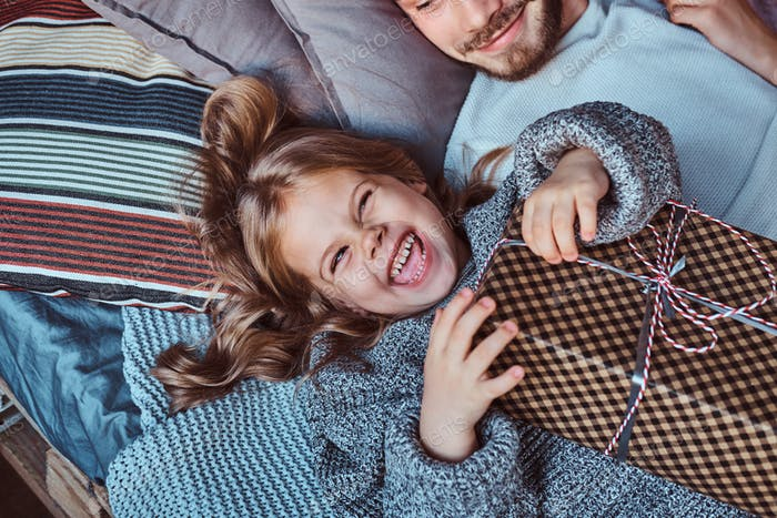 Close-up portrait of a happy little girl in warm sweater holds gifts while lying on bed.