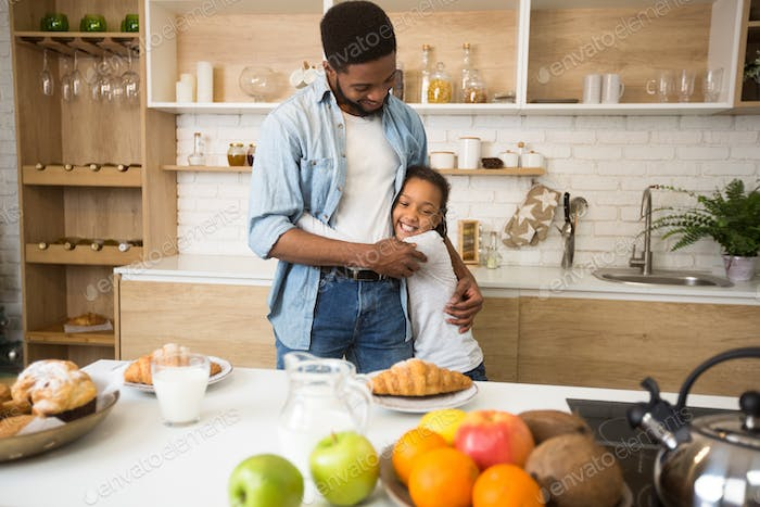 Thankful afro girl hugging her dad before breakfast