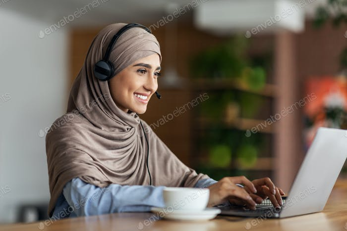 Smiling muslim girl studying online at cafe