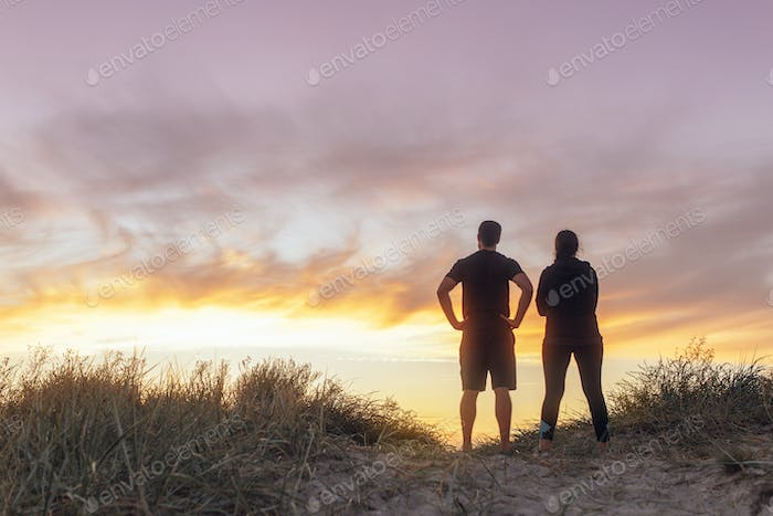 Rear view of couple standing on beach at sunset