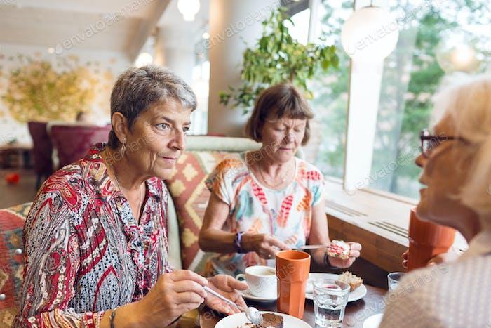 Three women taking coffee break in cafe