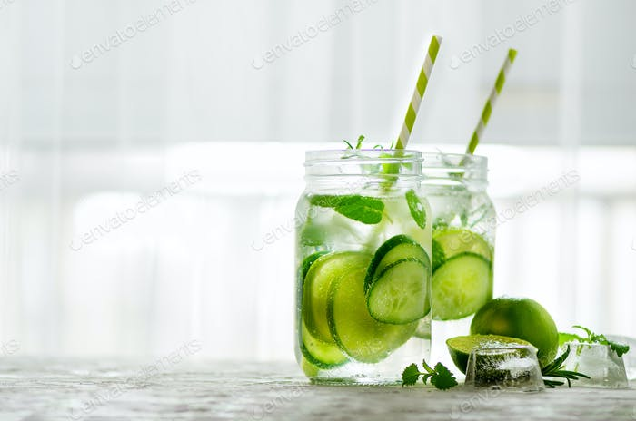 Homemade lime lemonade with cucumber, rosemary and ice, white background. Cold beverage for hot