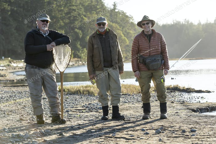 A portrait of two caucasian male fly fishermen and their fly fishing guide standing on a beach on