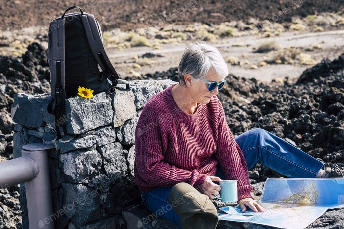 Active senior retirement lifestyle with beautiful mature caucasian lady sit down outdoor in travel