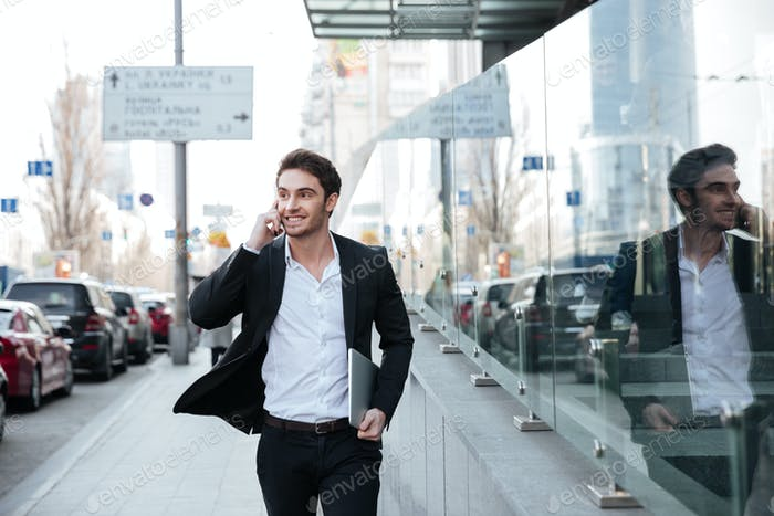 Smiling young businessman walking near business center