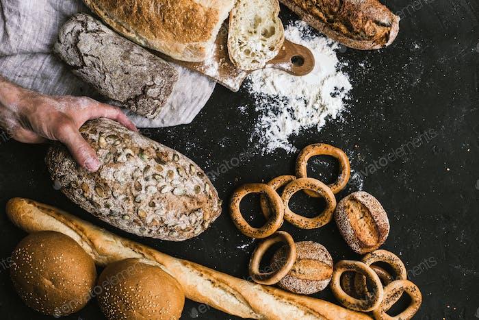 Bäckermann hält einen rustikalen Bio Laib Brot in den Händen