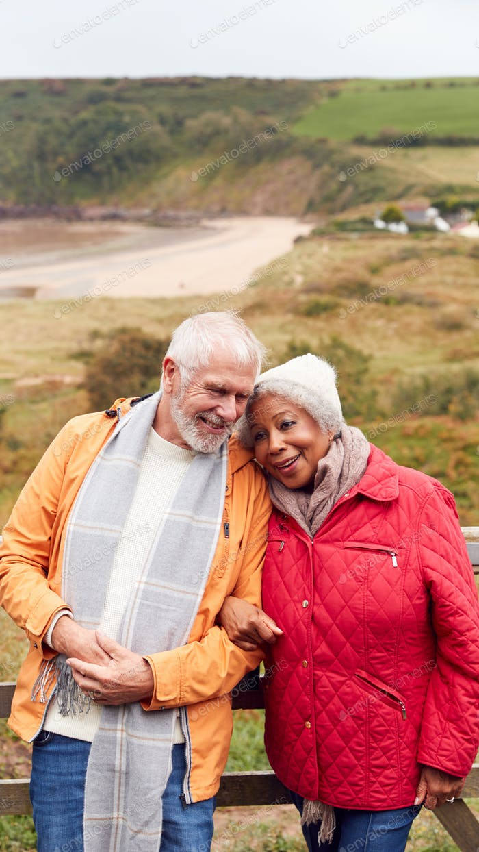 Loving Active Senior Couple Resting By Gate As They Walk Along Coastal Path In Winter