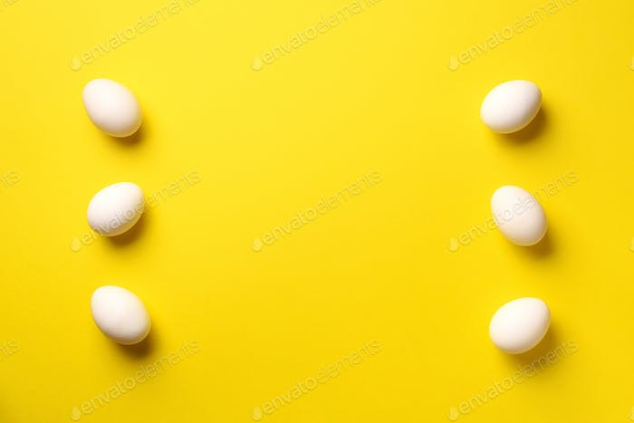 Food concept with white chicken eggs on yellow background. Top view. Creative pattern in minimal