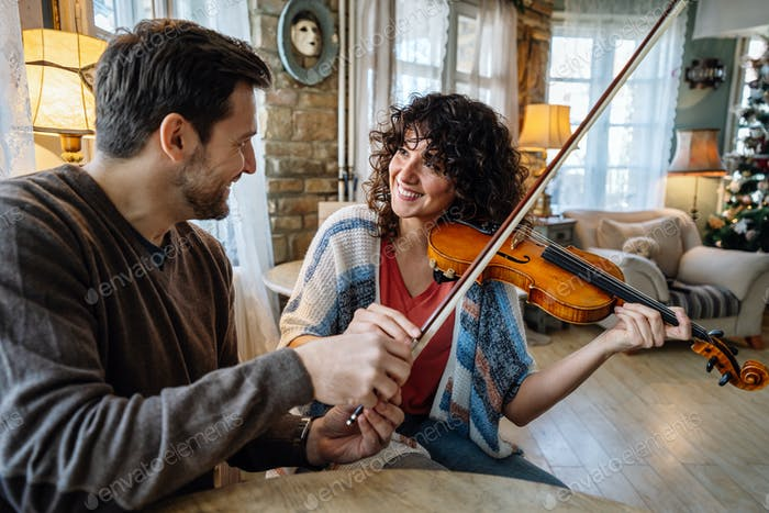 Violin teacher helping a woman student at home