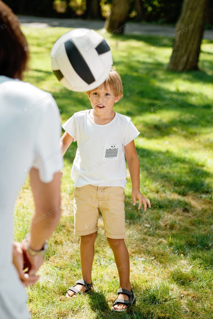 Summer time little boy dressed in the white t shirt is looking forward at the football ball flying