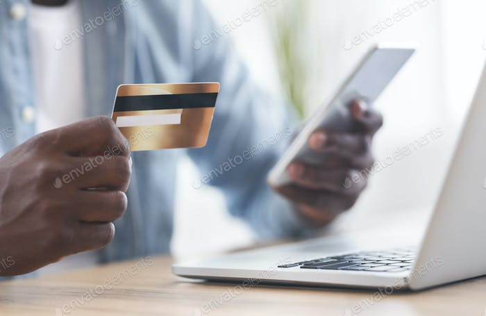 Black man using card and smartphone for paying bills online