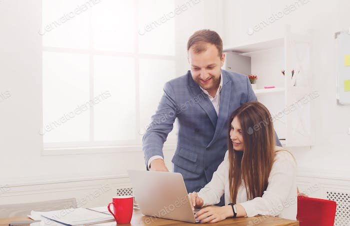 Businessman supervising his female assistant's work on laptop
