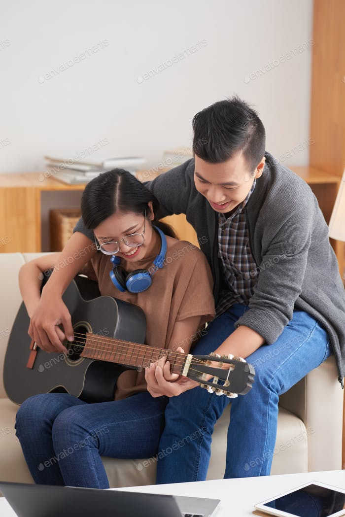 Young couple playing guitar at home