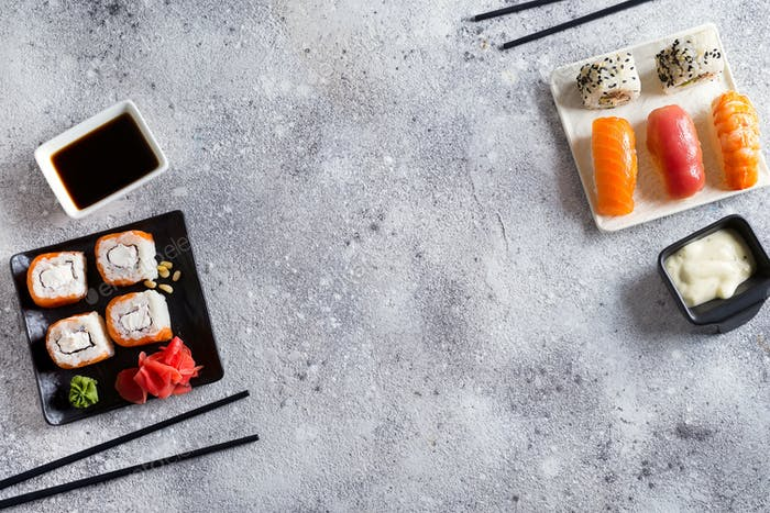 Various Fresh and delicious sushi set on black and white slate with metal and slate sticks, sauce on